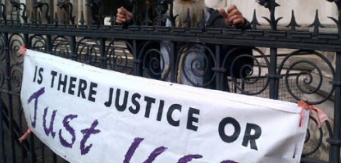 An MHRN supporter outside the Royal Courts of Justice with a banner that says 'Is there justice or just us?'