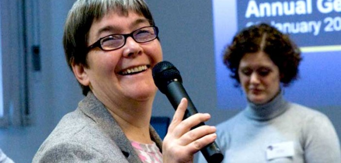 Sue Bott, holding a microphone