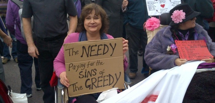 Protester in wheelchair holding sign saying 'The needy, paying for the sins of the greedy'