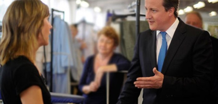 David Cameron talking to a woman in a workshop