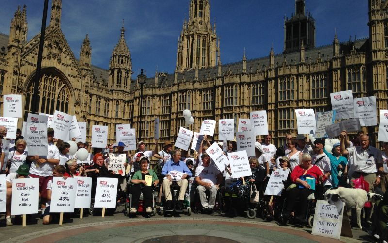 Campaigners with placards from Not Dead Yet UK, protesting about plans to legalise assisted suicide outside parliament