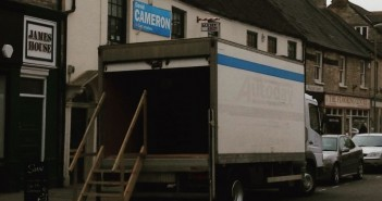 Lorry with stairs leading up to it, and Vote Cameron poster on wall of building behind