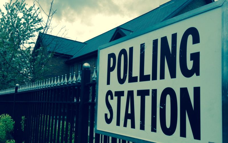 Polling station sign attached to metal railings