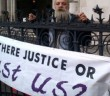 Roy Bard in front of a banner saying 'Is There Justice Or Just Us?'