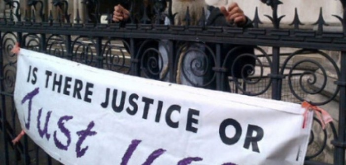 A protester in front of a banner saying 'Is There Justice Or Just Us?'