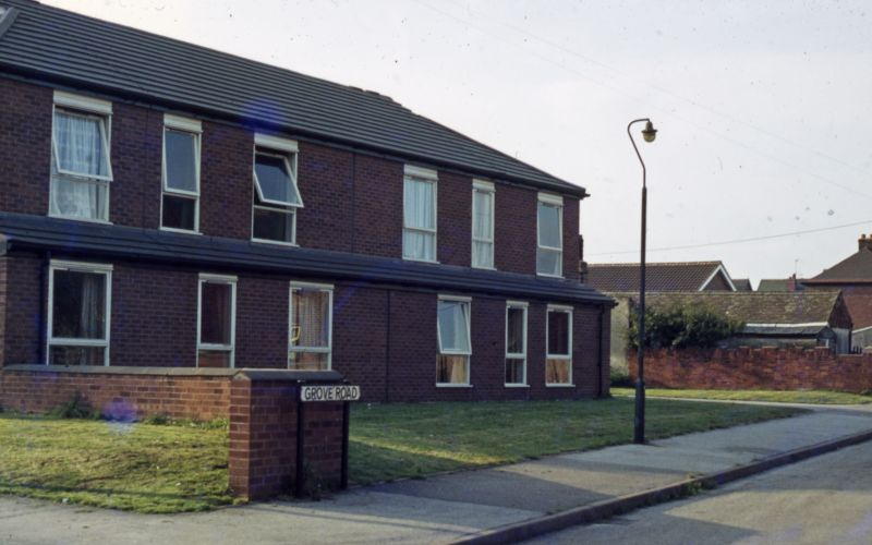 Two-storey block of flats, with road sign in front saying Grove Road