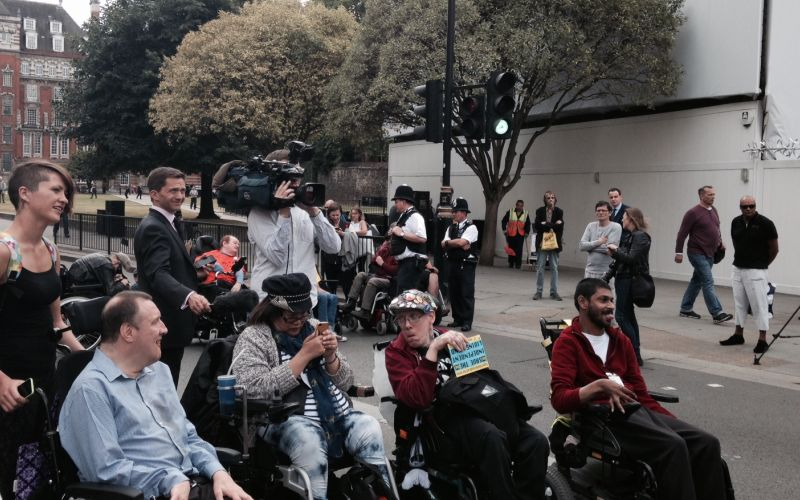 Four wheelchair-users blocking the road outside Parliament, with TV camera behind