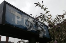 An old, overgrown sign saying Police