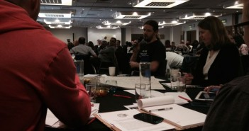 Delegates listen as a man talks into a microphone