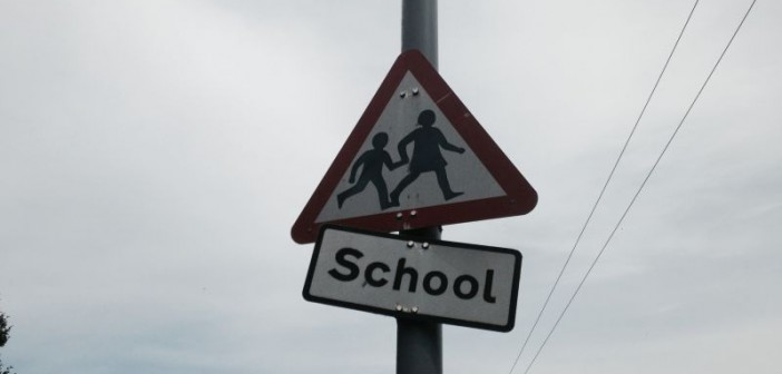 Triangular sign warning of a school ahead