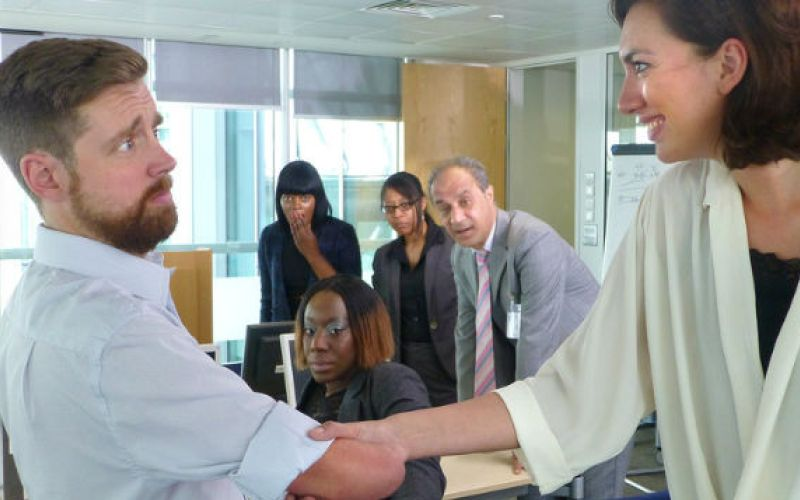 Bemused limbless man shakes hands with woman, while four office colleagues look on