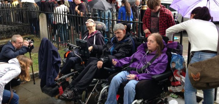 Three wheelchair-users sit in the rain in front of a fence,