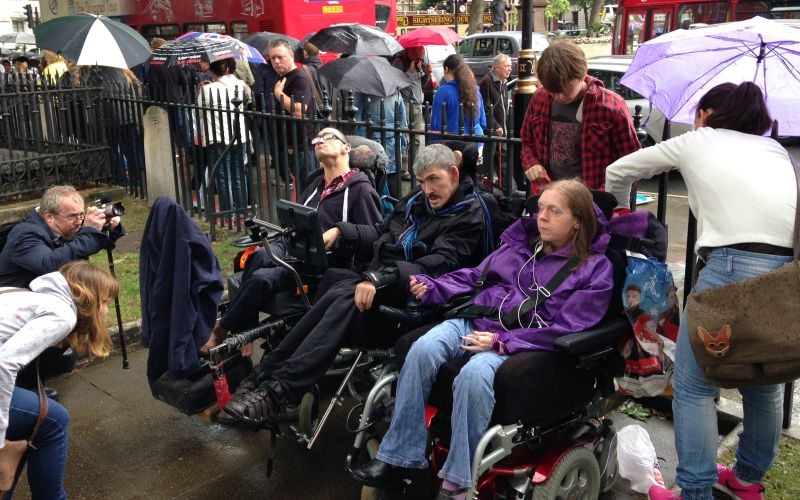 Three wheelchair-users in front of a metal fence, having their pictures taken