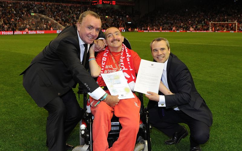 John Smith in his wheelchair being presented with a certificate in the middle of the pitch, flanked by two other men