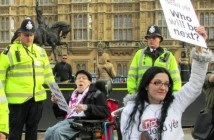 Two wheelchair-users protesting outside parliament, one of them (Dennis Queen) is holding a placard saying 'who will be next', and is wearing a Not Dead Yet UK tee-shirt