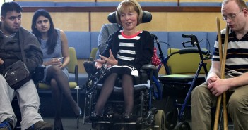 Baroness Campbell in her wheelchair, with two other disabled people on either side listening