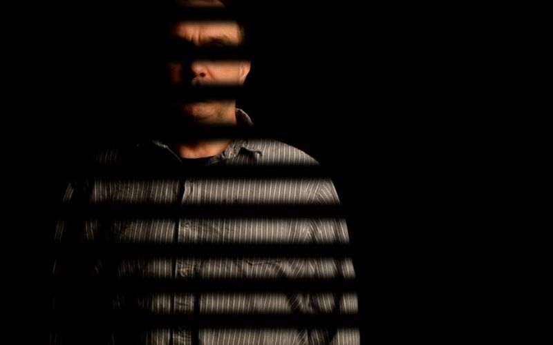 Man with part of face and body obscured by dark bars