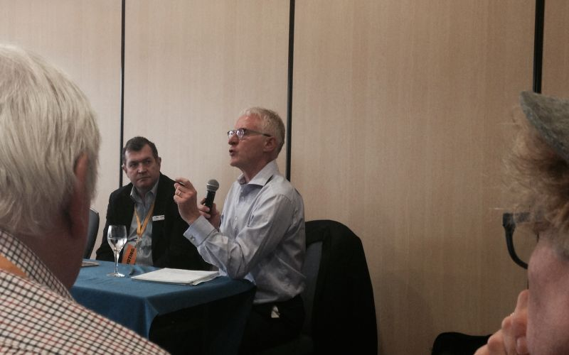 Norman Lamb, seated, speaking into a microphone
