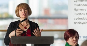 Rhian Davies speaking at a lectern, with a BSL interpreter beside her