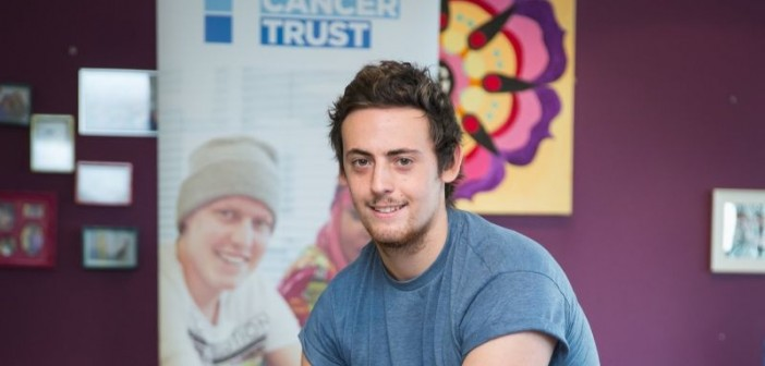 Tom Carter head and shoulders in front of a poster for the Teenage Cancer Trust