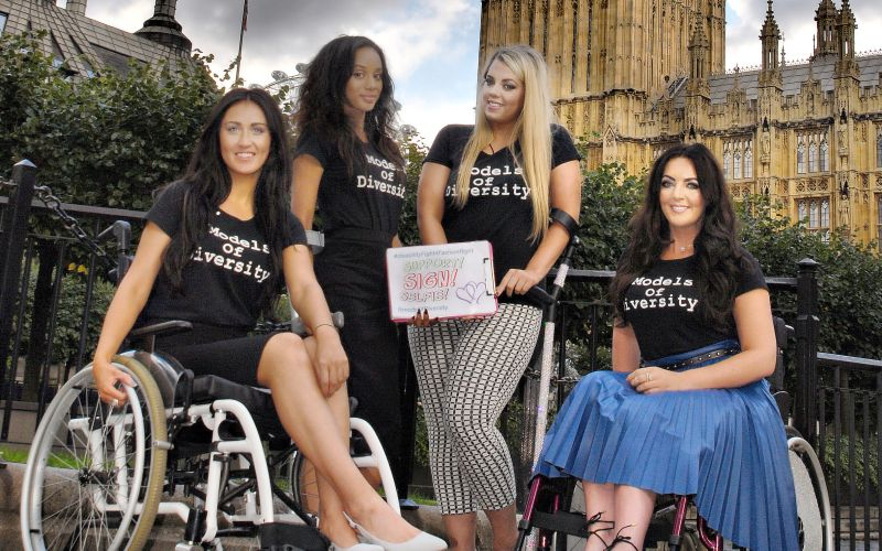 The four models posing with the petition outside parliament