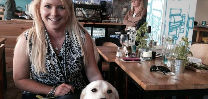 Jenny Nedwell sitting in restaurant with guide dog