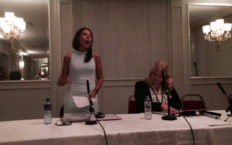 Debbie Abrahams standing behind a table, speaking into a microphone