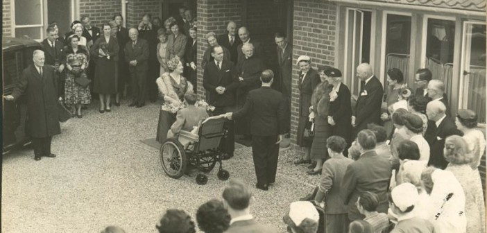 People watching the Queen Mother talking to a wheelchair-user, black and white photo