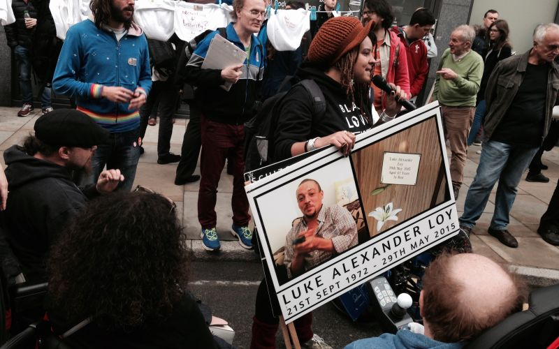 Natalie Jeffers speaking while holding a placard featuring a photo of her brother, watched by other protesters