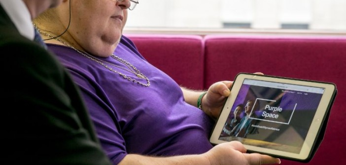 A woman in a purple shirt looking at the PurpleSpace website on a tablet
