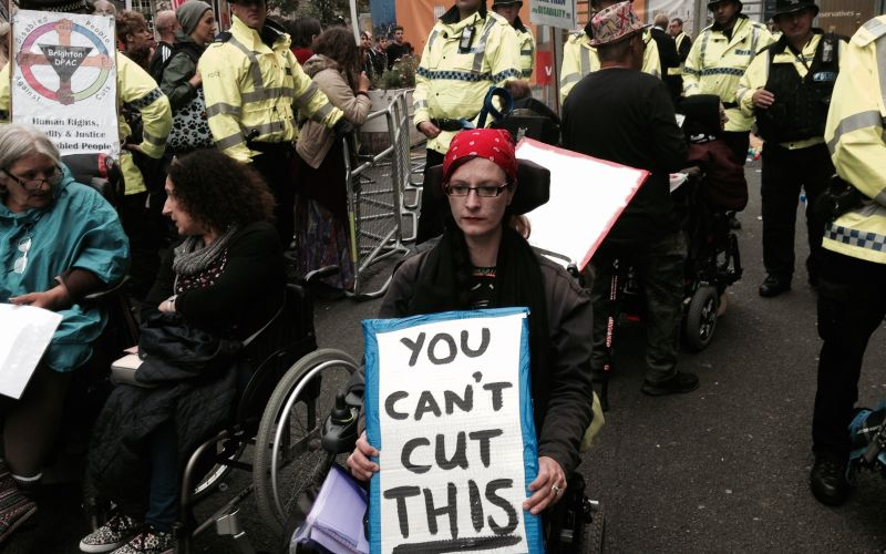 A wheelchair-user at a protest holding a placard saying 'You Can't Cut This'