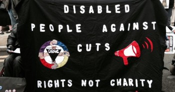 A protester holds up a banner saying Disabled People Against Cuts, Rights Not Charity