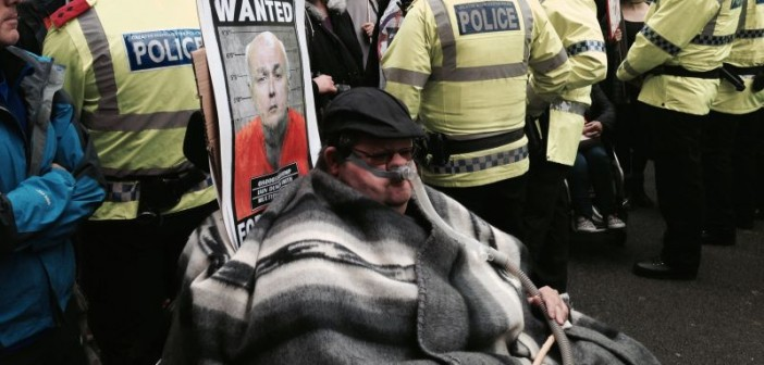 A wheelchair-user wearing a ventilator, with an Iain Duncan Smith 'Wanted' poster behind his head and surrounded by police