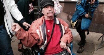 Bob Williams-Findlay, wearing a cap, in his wheelchair at a protest