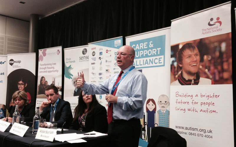 Alistair Burt speaking at a meeting in front of a Care and Support Alliance poster