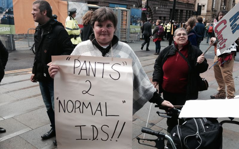Paula Peters holding a sign saying 'Pants 2 Normal IDS'