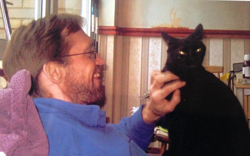 Stephen Carre smiling and stroking a black cat