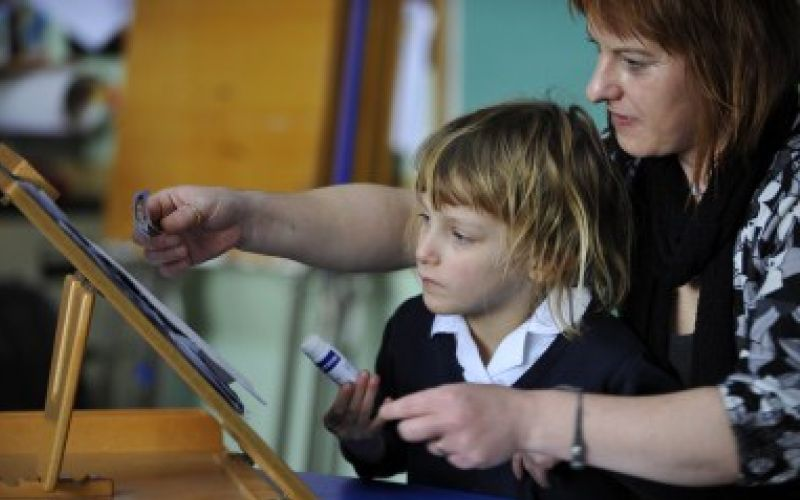 A child being helped by a teacher in an art lesson