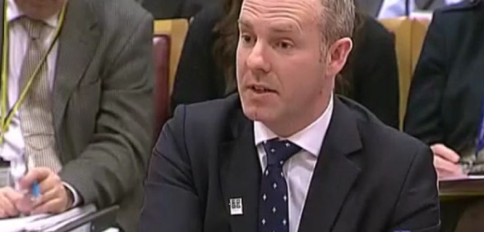 Head and shoulders of Justin Tomlinson giving evidence to a parliamentary committee