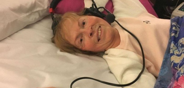Jane Campbell lying in her bed wearing headphones