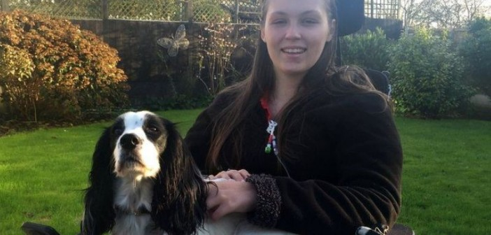 Lucy Watts in a wheelchair in a garden, with a dog on her lap