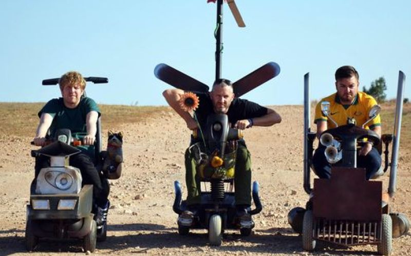 The three presenters of The Last Leg riding mobility scooters in the Outback