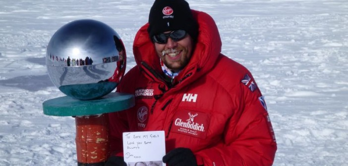 Duncan Slater at the South Pole carrying a photograph of his wife and daughter