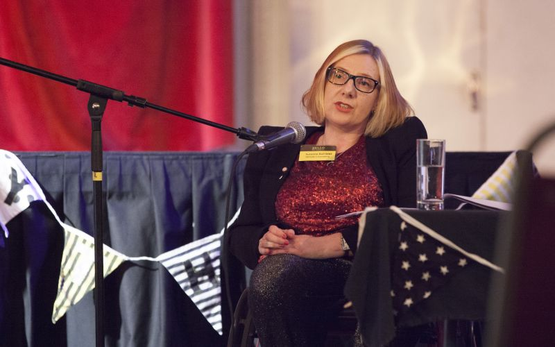 Suzanne Bull speaking into a microphone from her wheelchair