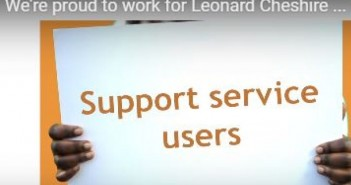 Someone from Leonard Cheshire holds up a card that says 'Support service users'