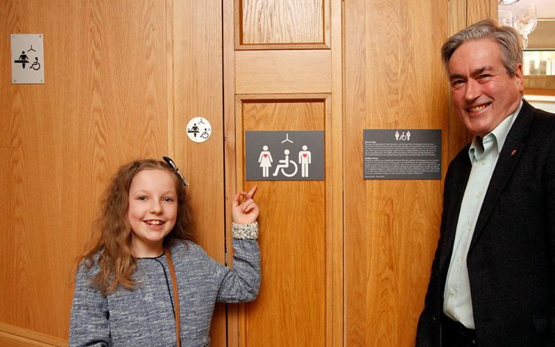 Grace points to sign on toilet door, watched by Iain Gray