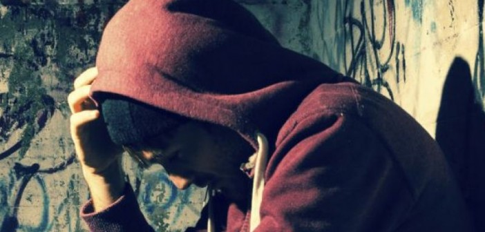 A young man wearing a hoodie, slumped in an alleyway