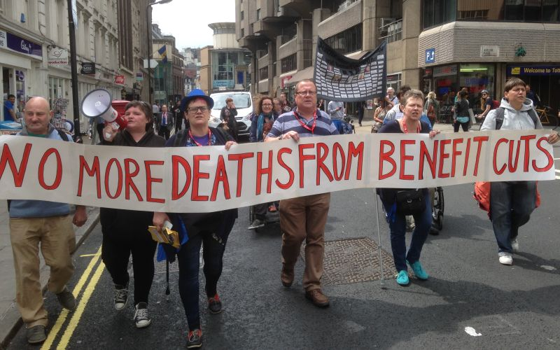 Five activists carrying a banner saying No More Deaths From Benefit Cuts