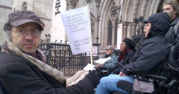Gabriel Pepper holding a sign warning that the class war is now on because of repeated attacks on vulnerable people