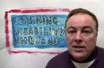 Gary Bourlet in front oif a sign saying Learning Disability England